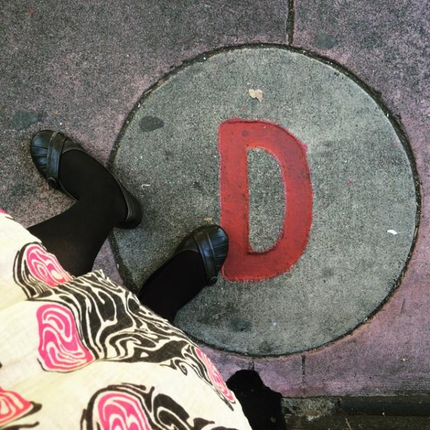 letter D in sidewalk outside school